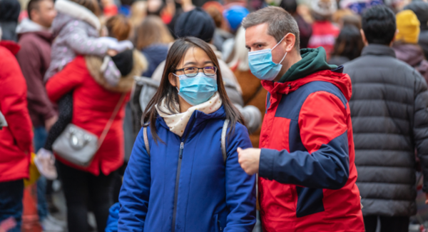 Man and woman in a crowd wearing facemasks