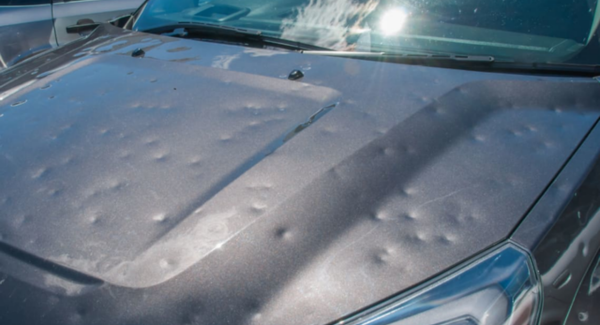 Car bonnet covered in dents caused by hail stones